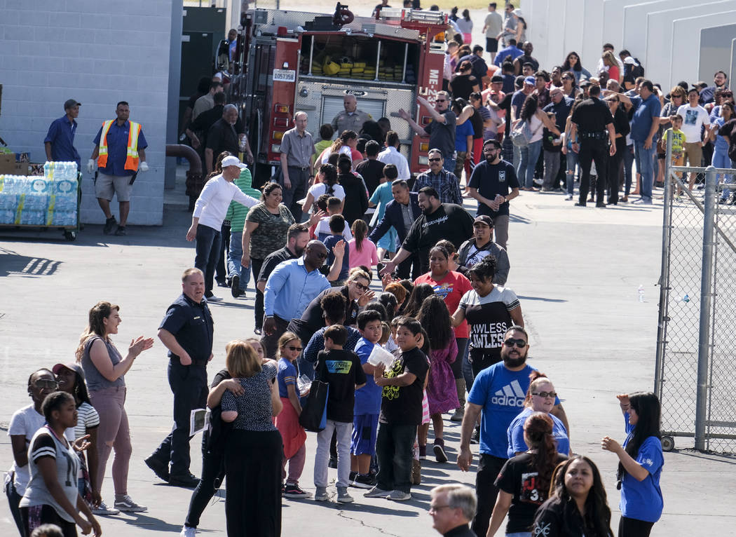 School staff greet students at North Park Elementary School, in relief at Cajon High School, Monday, April 10, 2017, in San Bernardino, Calif., after a deadly shooting occurred at the elementary s ...