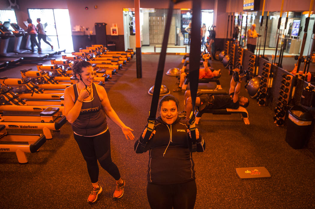 Coach Crystal Banda, left, helps Jennifer Tydingco with resistance bands during a training session at Orangetheory Fitness on Wednesday, April 5, 2017, in Las Vegas. (Benjamin Hager/Las Vegas Revi ...