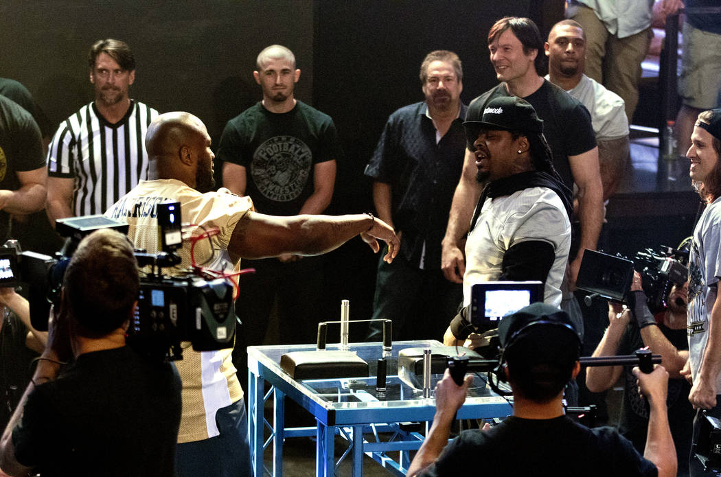 Team coaches and former NFL players James Harrison, gold jersey, and Marshawn Lynch, silver jersey, smack talk at the inaugural Pro Football Armwrestling Championship, which was filmed at the MGM  ...