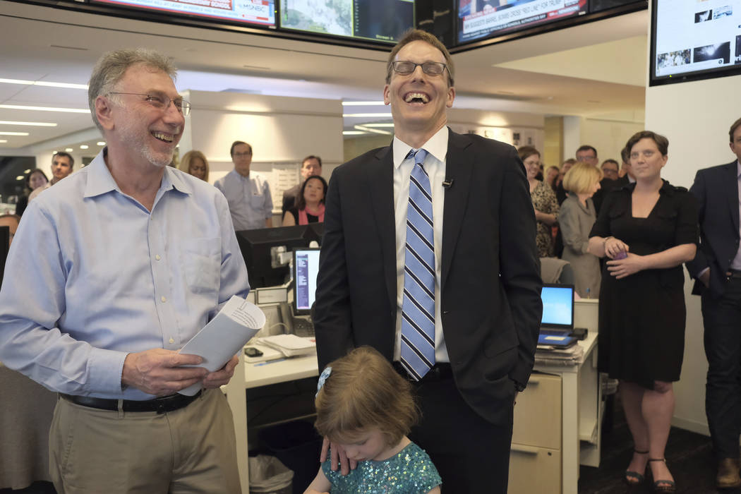 Washington Post editor Martin Baron, left, joins the paper's staff in congratulating David Fahrenthold, center, upon learning that he won the Pulitzer Prize for National Reporting, for dogged repo ...