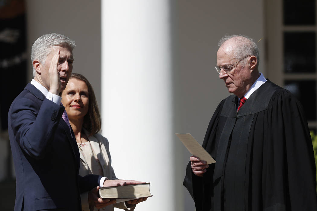Supreme Court Justice Anthony Kennedy administers the judicial oath to Justice Neil Gorsuch during a re-enactment in the Rose Garden of the White House White House in Washington, Monday, April 10, ...