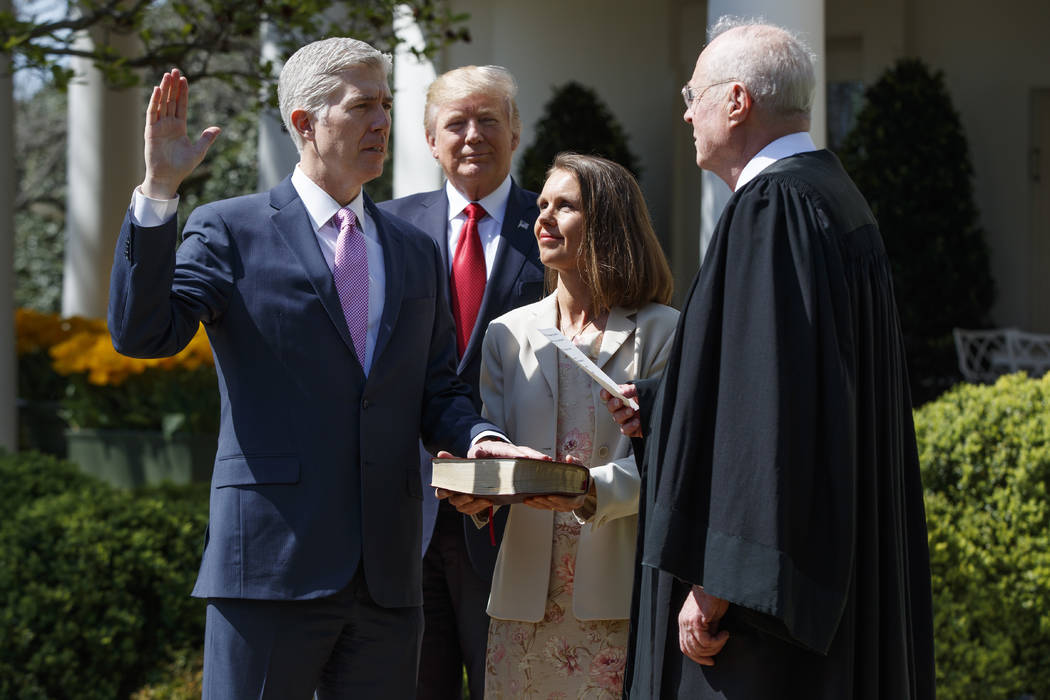 President Donald Trump watches as Supreme Court Justice Anthony Kennedy administers the judicial oath to Judge Neil Gorsuch during a re-enactment in the Rose Garden of the White House, Monday, Apr ...