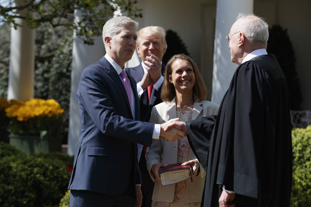 President Donald Trump watches as Supreme Court Justice Anthony Kennedy shakes hands with Justice Neil Gorsuch during a public swearing-in ceremony for Gorsuch, accompanied by his wife Marie Louis ...