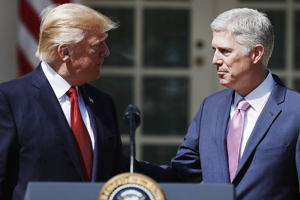 President Donald Trump looks to new Supreme Court Justice Neil Gorsuch in the Rose Garden of the White House White House in Washington, Monday, April 10, 2017, following a public swearing-in cerem ...