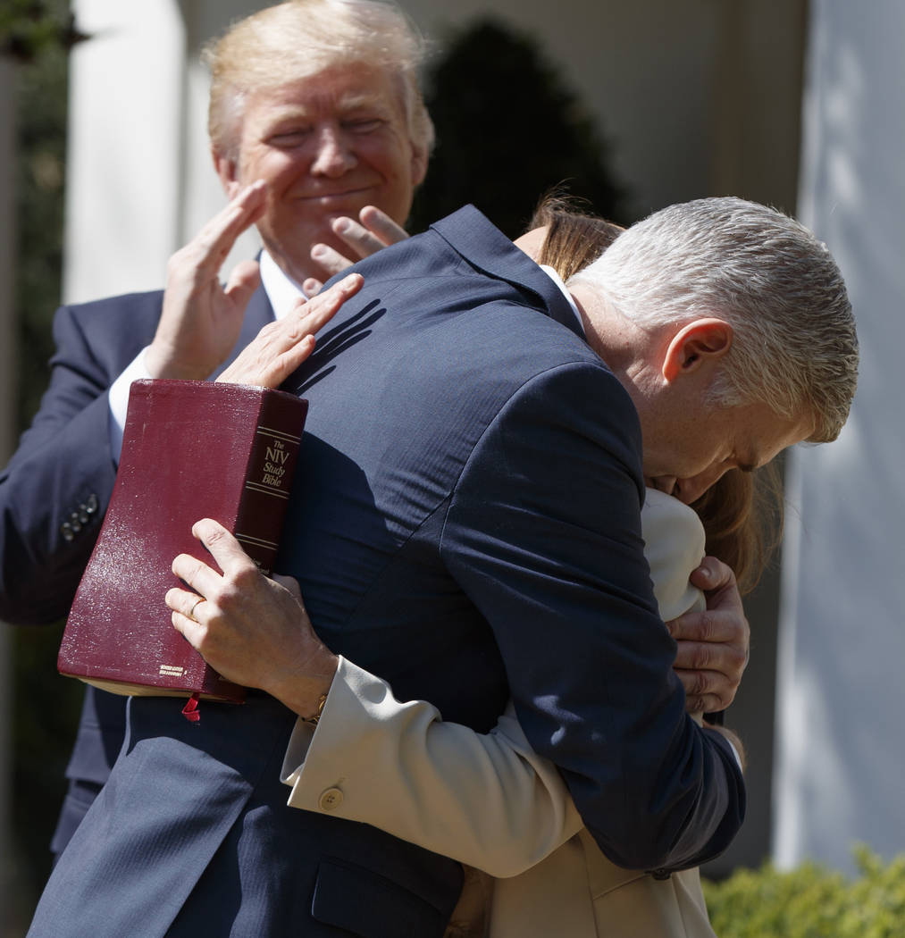 President Donald Trump applauds as new Supreme Court Justice Neil Gorsuch hugs his wife Marie Louise Gorsuch during a public swearing-in ceremony in the Rose Garden of the White House in Washingto ...