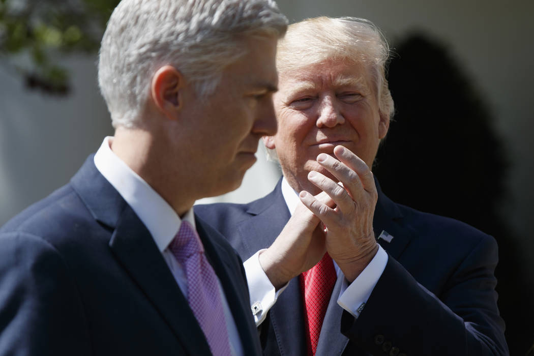 President Donald Trump applauds new Supreme Court Justice Neil Gorsuch during a public swearing-in ceremony for Gorsuch in the Rose Garden of the White House in Washington, Monday, April 10, 2017. ...