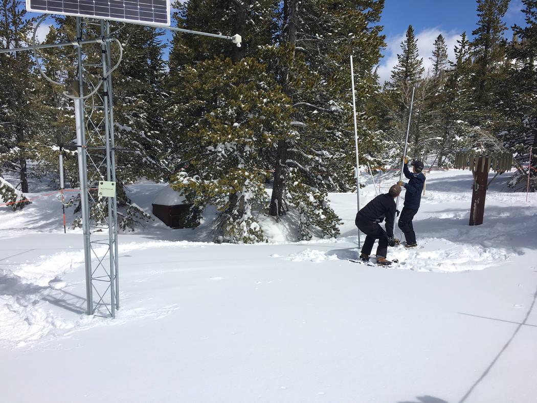 It takes several tries before Jim Gifford, left, and Jeff Anderson, both with the Natural Resources Conservation Service, finlly hit the bottom of the snow pack at a Mount Rose measuring station o ...