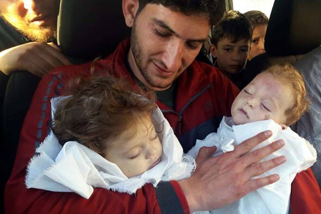 In this picture taken on Tuesday April 4, 2017, Abdul-Hamid Alyousef, 29, holds his twin babies who were killed during a chemical weapons attack, in Khan Sheikhoun in the northern province of Idli ...