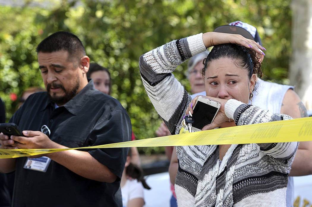 Parents and family of North Park Elementary School students stand across the street from the school waiting to hear from their children after a fatal shooting at the school in San Bernardino, Cali ...