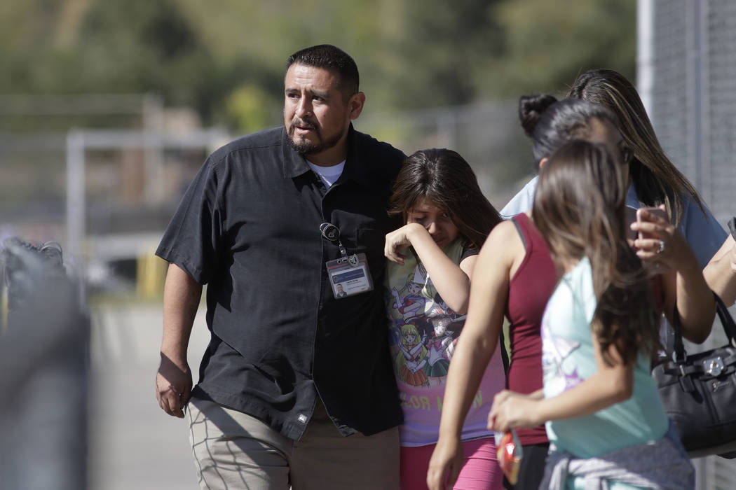 Camilo Rocha, left, comforts his daughter, Serina, a 11-year-old student at North Park Elementary School, after they were reunited at Cajon High School, Monday, April 10, 2017, in San Bernardino,  ...