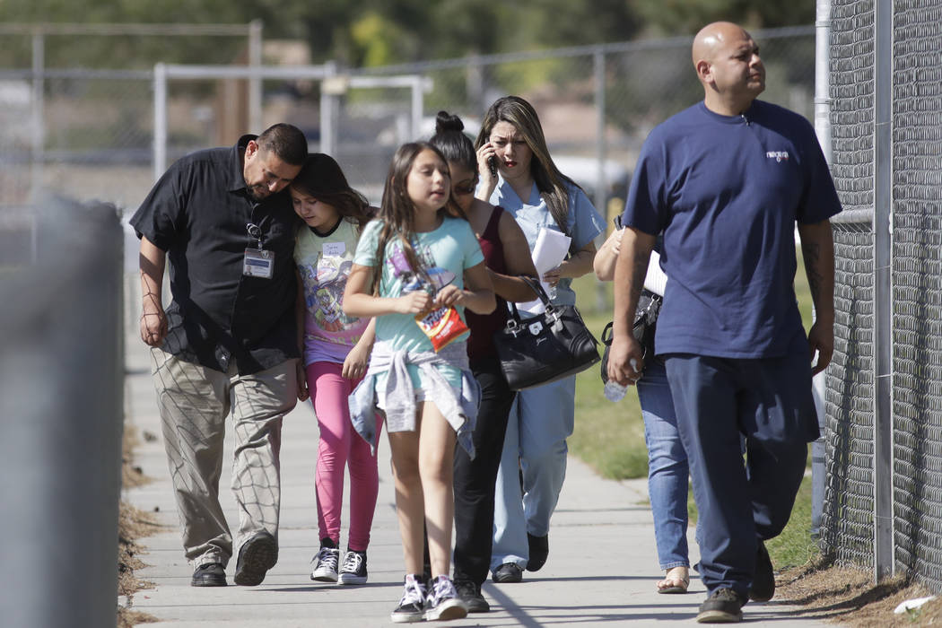 Camilo Rocha, left, comforts his daughter, Serina, an 11-year-old student at North Park Elementary School, after they were reunited at Cajon High School, Monday, April 10, 2017, in San Bernardino, ...