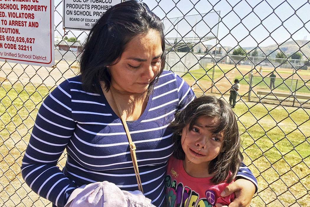 Elizabeth Barajas hugs her daughter, Marissa Perez, 9, following their reunion as Marissa recounted her experiences being in the classroom in which her teacher was shot to death at North Park Elem ...