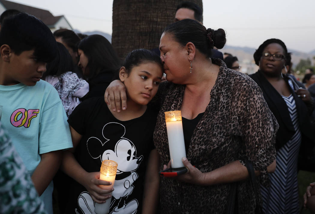 Betty Rodriguez, right, comforts her granddaughter Giselle during a prayer service held to honor the shooting victims at North Park Elementary School, Monday, April 10, 2017, in San Bernardino, Ca ...