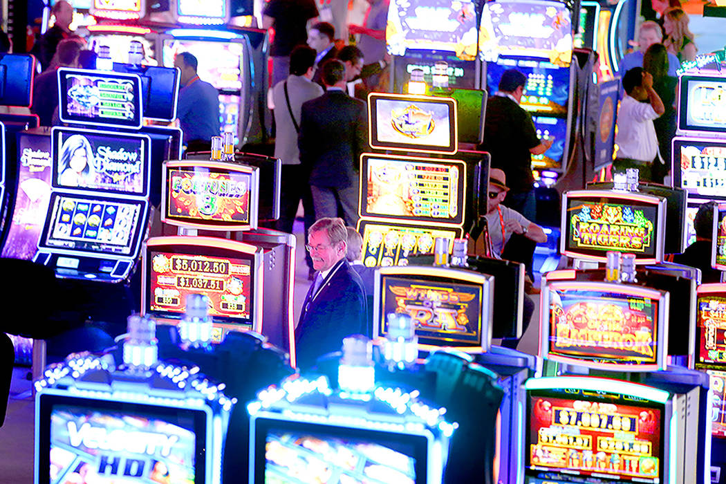 People looks at themed slot machines in the Scientific Games booth during the Global Gaming Expo at the Las Vegas Sands Expo and Convention Center on Thursday , Sept. 29, 2016. Scientific Games ha ...