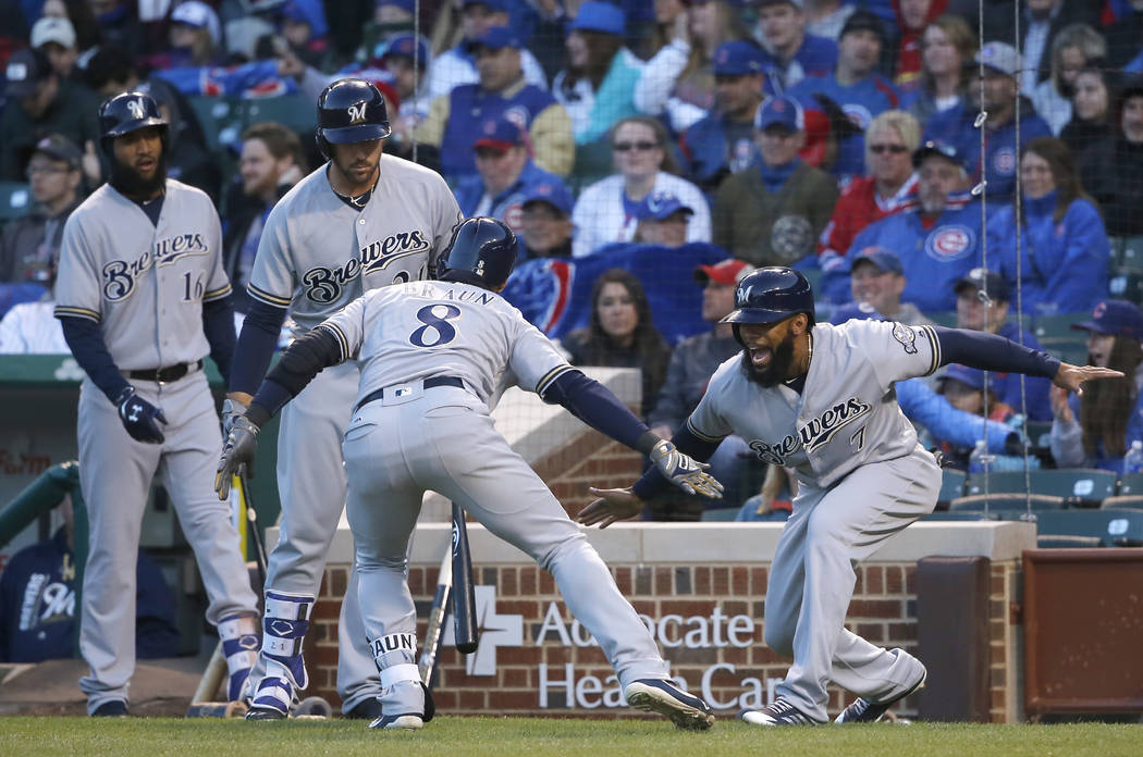 Milwaukee Brewers' Ryan Braun (8) celebrates his two-run home run with Eric Thames (7) as Domingo Santana (16) and Travis Shaw watch during the first inning of a baseball game against the Chicago  ...