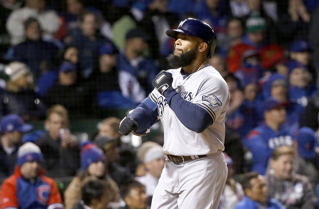 Milwaukee Brewers' Eric Thames celebrates his home run off Chicago Cubs starting pitcher John Lackey, during the third inning of a baseball game Monday, April 17, 2017, in Chicago. (AP Photo/Charl ...