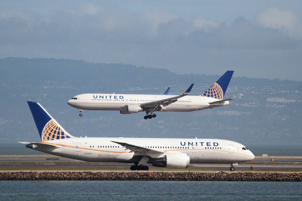 A United Airlines jet taxis as another lands at San Francisco International Airport. (Louis Nastro/Reuters)
