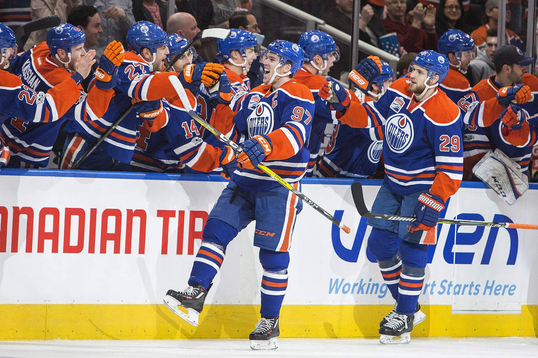 Edmonton Oilers' Connor McDavid (97) and Leon Draisaitl (29) celebrate a goal against the Vancouver Canucks during the third period of an NHL hockey game in Edmonton, Alberta, Sunday, April 9, 201 ...