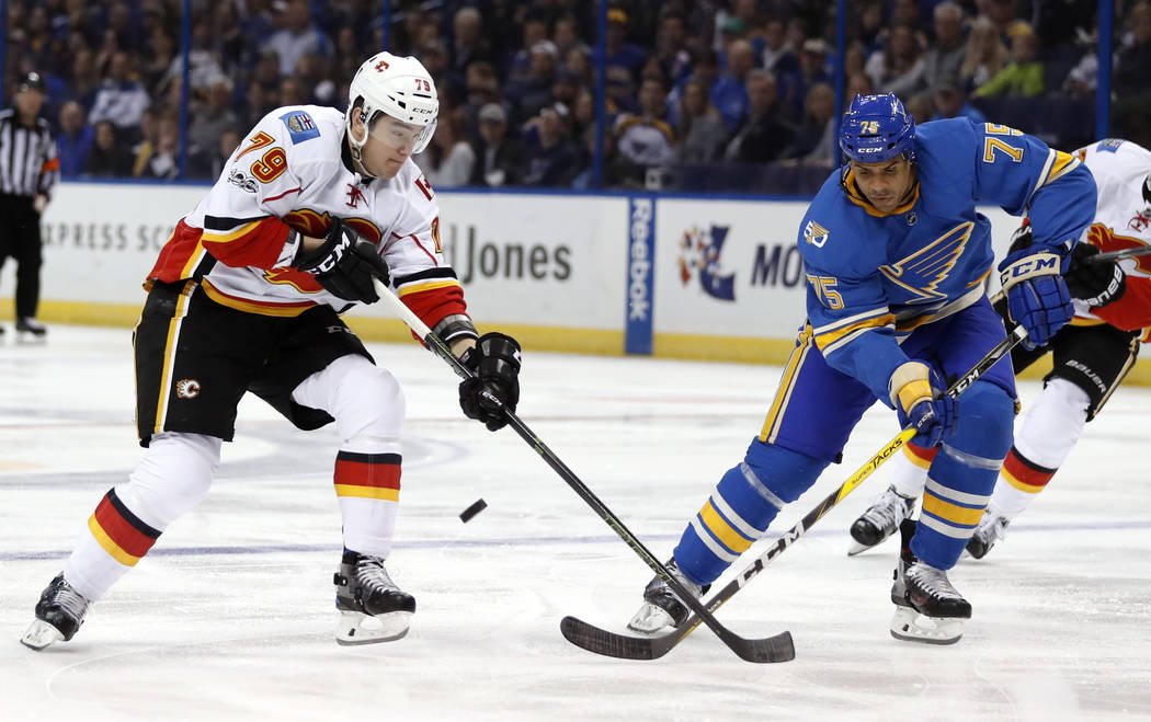 Calgary Flames' Micheal Ferland (79) and St. Louis Blues' Ryan Reaves (75) chase after a loose puck during the first period of an NHL hockey game, Saturday, March 25, 2017, in St. Louis. (Jeff Rob ...