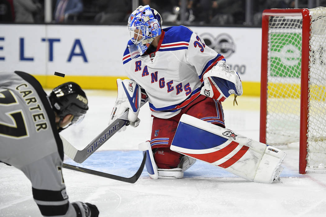 New York Rangers goalie Antti Raanta, right, of Finland, right, blocks a shot as Los Angeles Kings center Jeff Carter falls in front during the second period of an NHL hockey game, Saturday, March ...