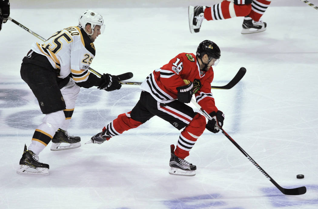 Chicago Blackhawks' Marcus Kruger (16), of Sweden, moves the puck down ice against Boston Bruins' Brandon Carlo (25) during the second period of an NHL hockey game Sunday, April 2, 2017, in Chicag ...