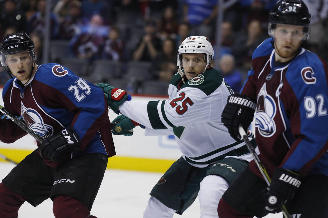 From left, Colorado Avalanche center Nathan MacKinnon (29), Minnesota Wild defenseman Jonas Brodin (25) and Colorado Avalanche left wing Gabriel Landeskog (92) in the third period of an NHL hockey ...