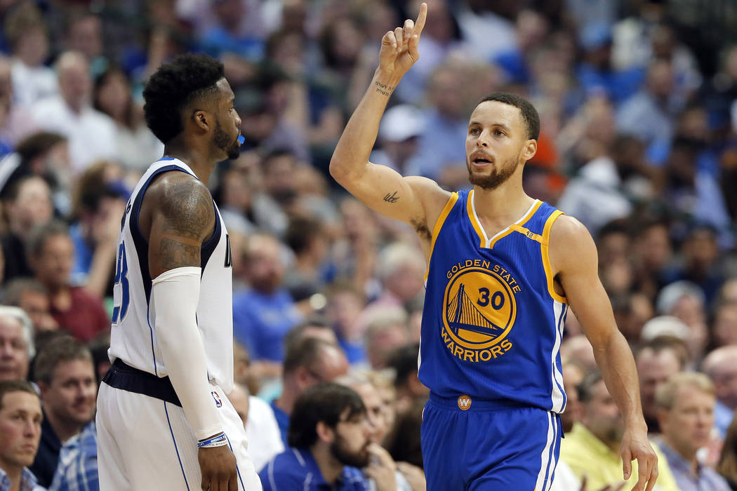 Dallas Mavericks guard Wesley Matthews (23) watches as Golden State Warriors' Stephen Curry (30) celebrates sinking a 3-point basket in the second half of an NBA basketball game, Tuesday, March 21 ...