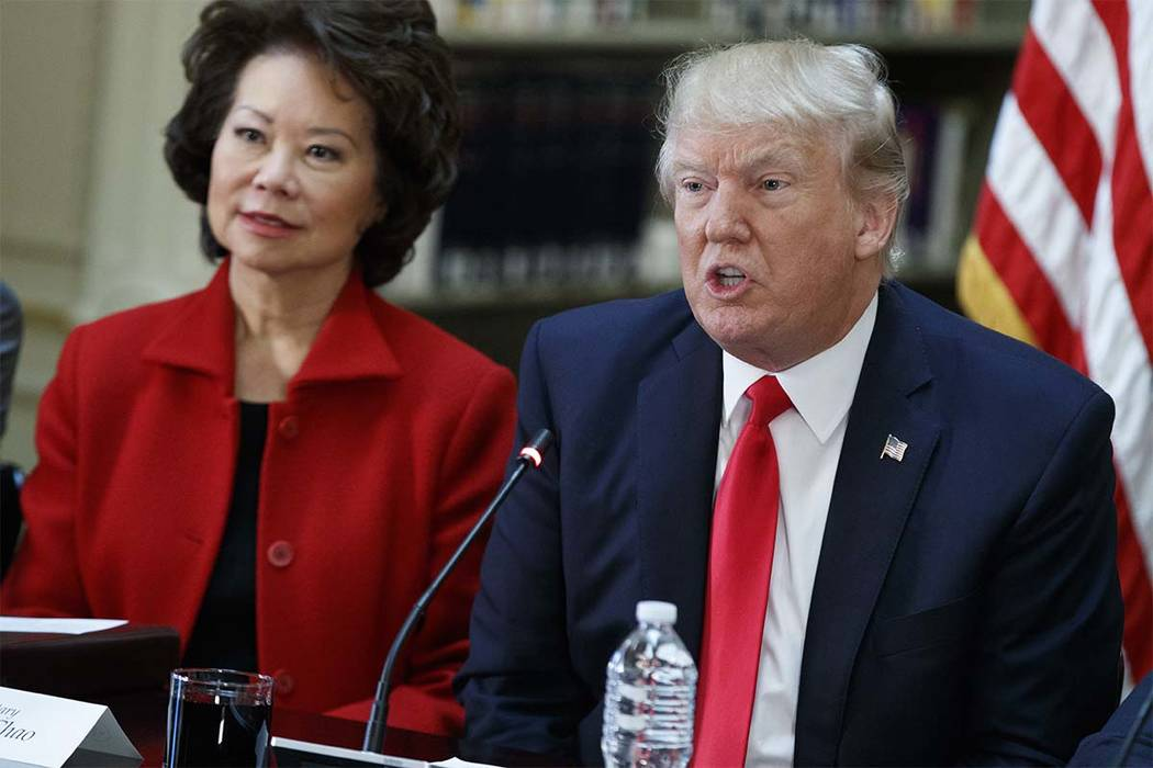 Transportation Secretary Elaine Chao listens at left as President Donald Trump speaks during a meeting with business leaders in the State Department Library of the Eisenhower Executive Office Buil ...