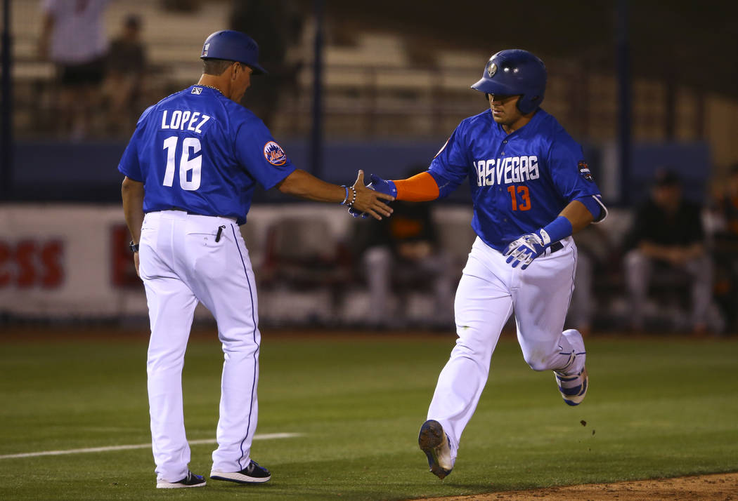 Las Vegas 51s shortstop Phillip Evans (13) celebrates his three-run home run with Las Vegas 51s manager Pedro Lopez (16) during the opening day game against Fresno at Cashman Field in Las Vegas on ...