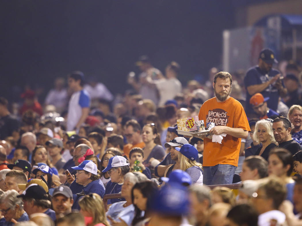 A Las Vegas 51s fan walks through the stands with food during the opening day game against the Fresno Grizzlies at Cashman Field in Las Vegas on Tuesday, April 11, 2017. Chase Stevens Las Vegas Re ...