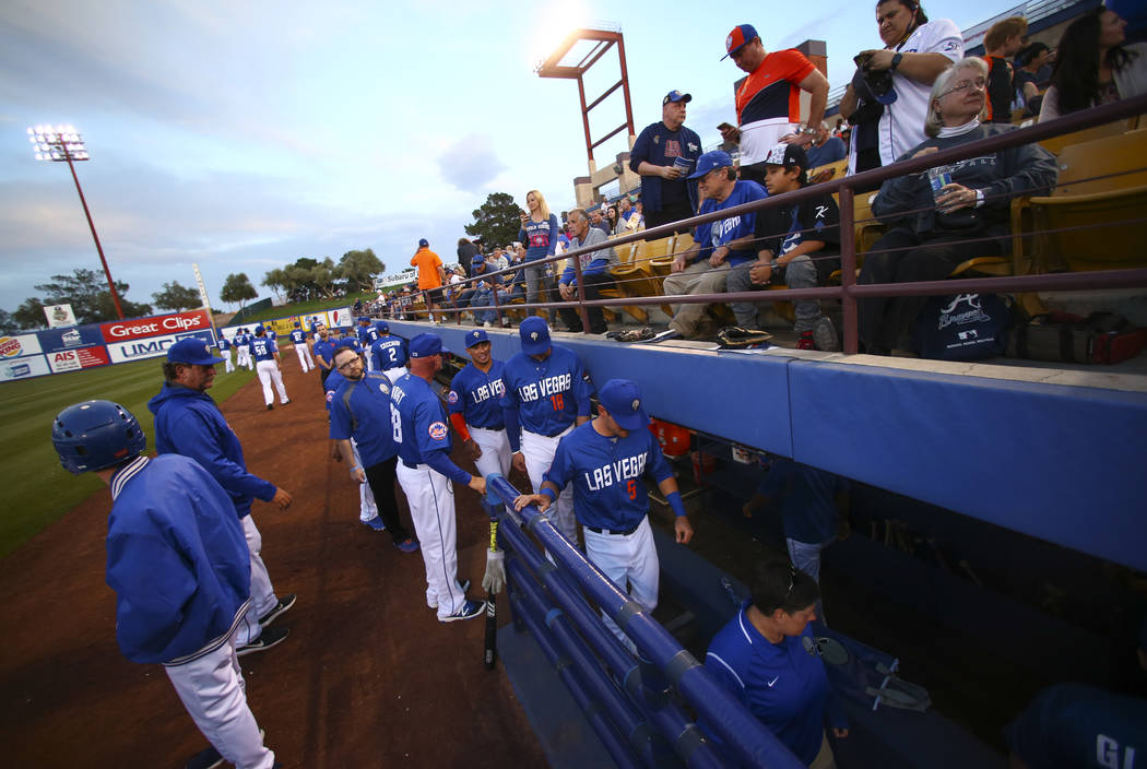 Las Vegas 51s players and staff head to the dugout for the start of their opening day game against the Fresno Grizzlies at Cashman Field in Las Vegas on Tuesday, April 11, 2017. Chase Stevens Las  ...