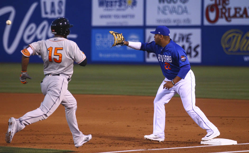 Las Vegas 51s infielder Dominic Smith (22) reaches out to catch a throw to get out Fresno Grizzlies outfielder Teoscar Hernandez (15) during the opening day game against Fresno at Cashman Field in ...