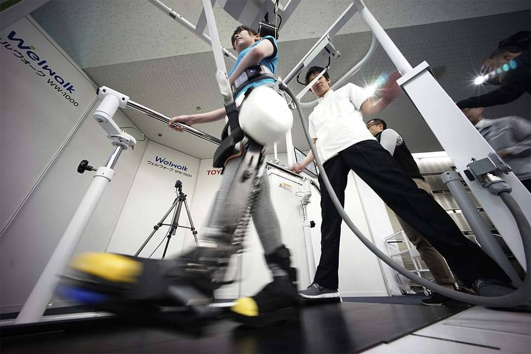 A model demonstrates the Welwalk WW-1000, a wearable robotic leg brace designed to help partially paralyzed people walk at the main system with treadmill and monitor at Toyota Motor Corp.'s head o ...