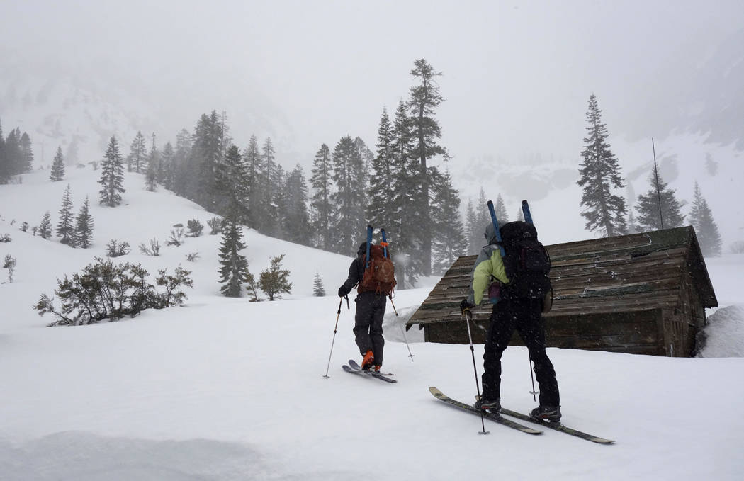 In this photo taken March 30, 2017, Kevin Klinefelter, left, and John Dittli, right, begin to ski toward Kearsarge Pass in Inyo National Forest near Independence, Calif., where they hoped to condu ...
