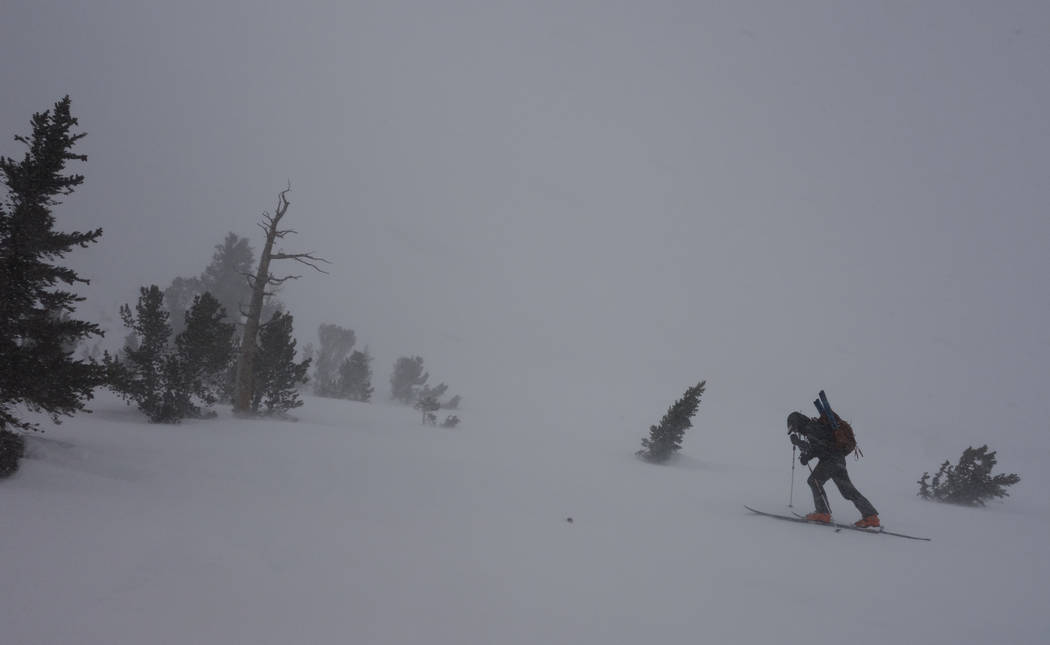 In this photo taken March 30, 2017, Kevin Klinefelter leans into the wind and driving snow as he climbs toward Kearsarge Pass in Inyo National Forest near Independence, Calif., where he hoped to c ...