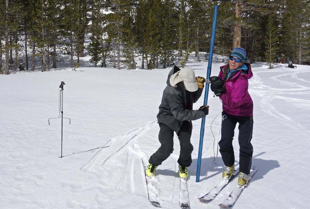 In this photo taken March 31, 2017, Kevin Klinefelter, left, and his wife Ann Klinefelter, right, work to measure snow depth and water content in the Dusy Basin area of Kings Canyon National Park  ...