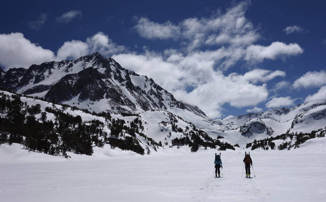 In this photo taken March 31, 2017, Ann Klinefelter, left, and her husband, Kevin Klinefelter, right, ski across a frozen lake during a California Cooperative Snow Survey in the Inyo National Fore ...