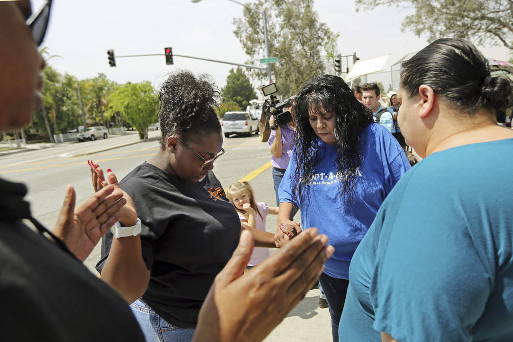 Marie Cabrera, second from right, leads a prayer group near a sidewalk memorial to the teacher and student who were shot to death Monday at North Park Elementary School in San Bernardino, Calif.,  ...