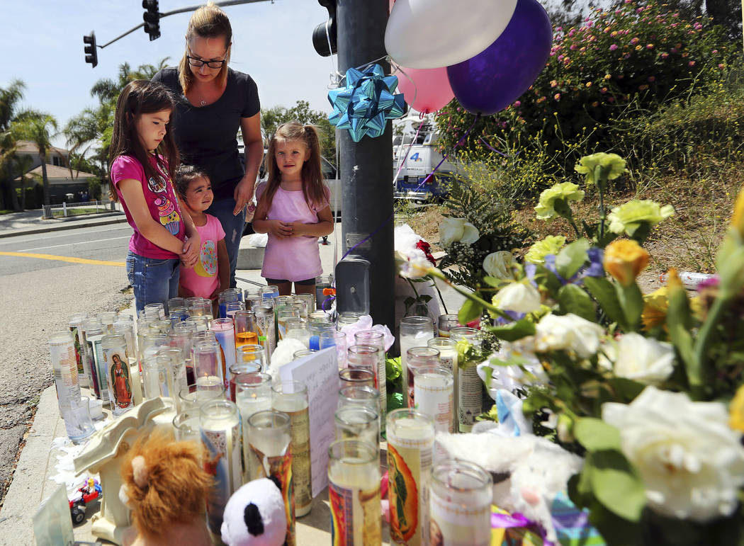 Lena Hammerling and her daughters Melissa, left, and Maci, right, and an unidentified child look at a sidewalk memorial dedicated to the teacher and student who were shot to death Monday at North  ...