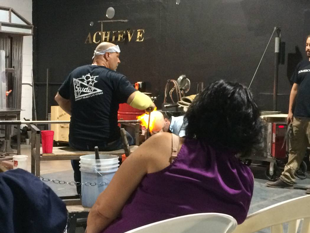An attendees leans right for a better view as Larry Domsky works his magic on a hot glass piece April 7, 2017, during an exhibition at Domsky Glass, 2758 S. Highland Drive. The studio usually crea ...