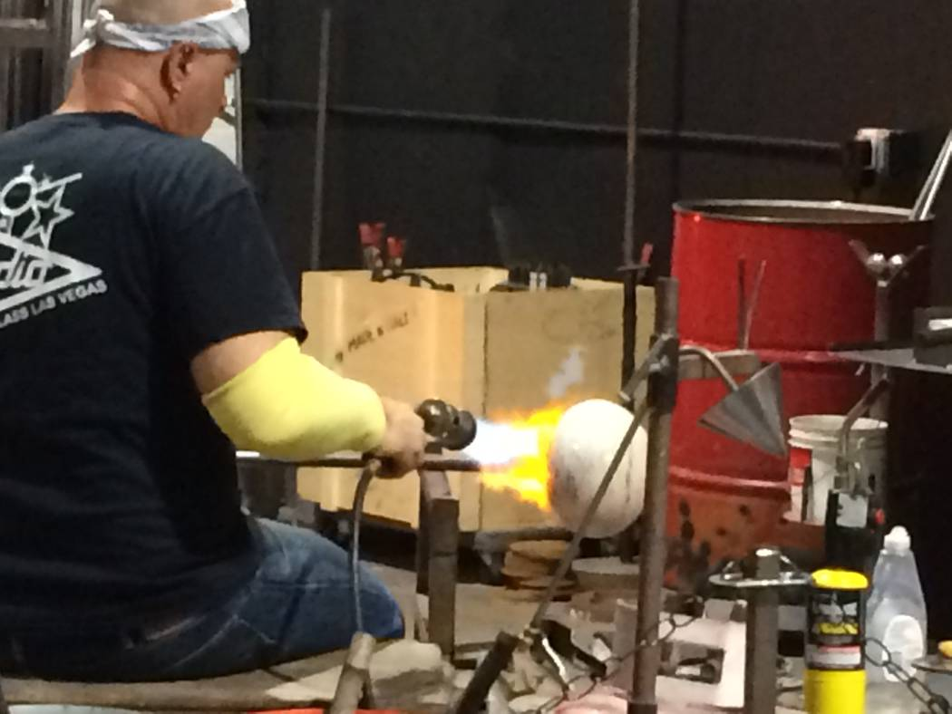 Larry Domsky uses a blow torch to keep the glass pliable April 7, 2017, during an exhibition at Domsky Glass, 2758 S. Highland Drive. Owned by Larry and his wife, Barbara, the studio usually creat ...