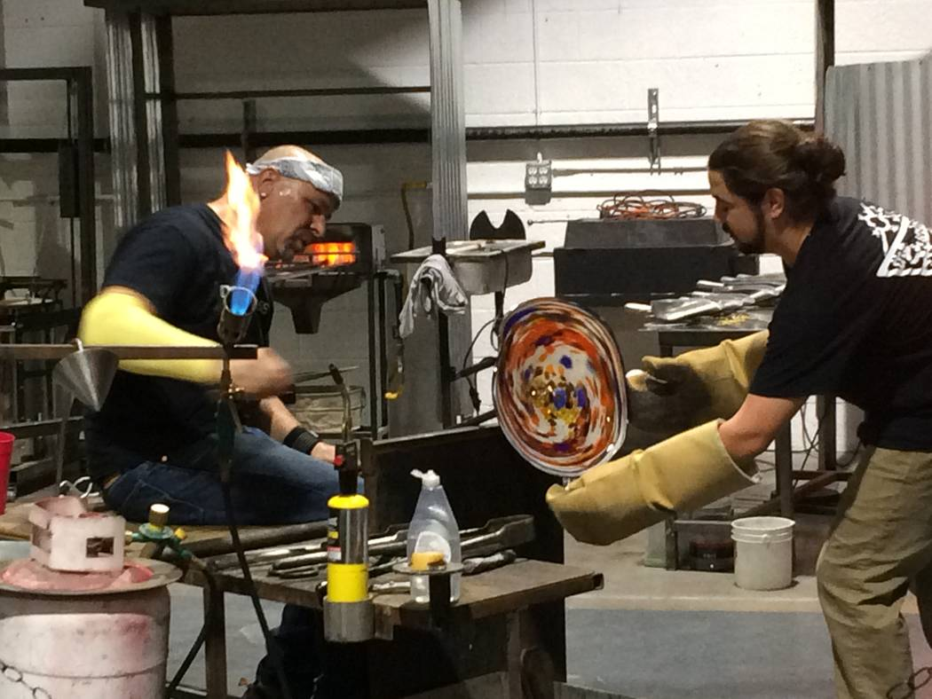 Larry Domsky, left, works the hot glass as assistant Matt Humphrey helps April 7, 2017, during an exhibition at Domsky Glass, 2758 S. Highland Drive. Owned by Larry and his wife, Barbara, the stud ...