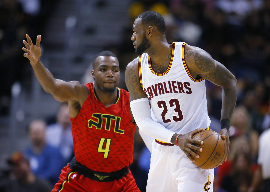 Cleveland Cavaliers forward LeBron James (23) is defended by Atlanta Hawks forward Paul Millsap (4) in the first half of an NBA basketball game on Sunday, April 9, 2017, in Atlanta. The Hawks won  ...