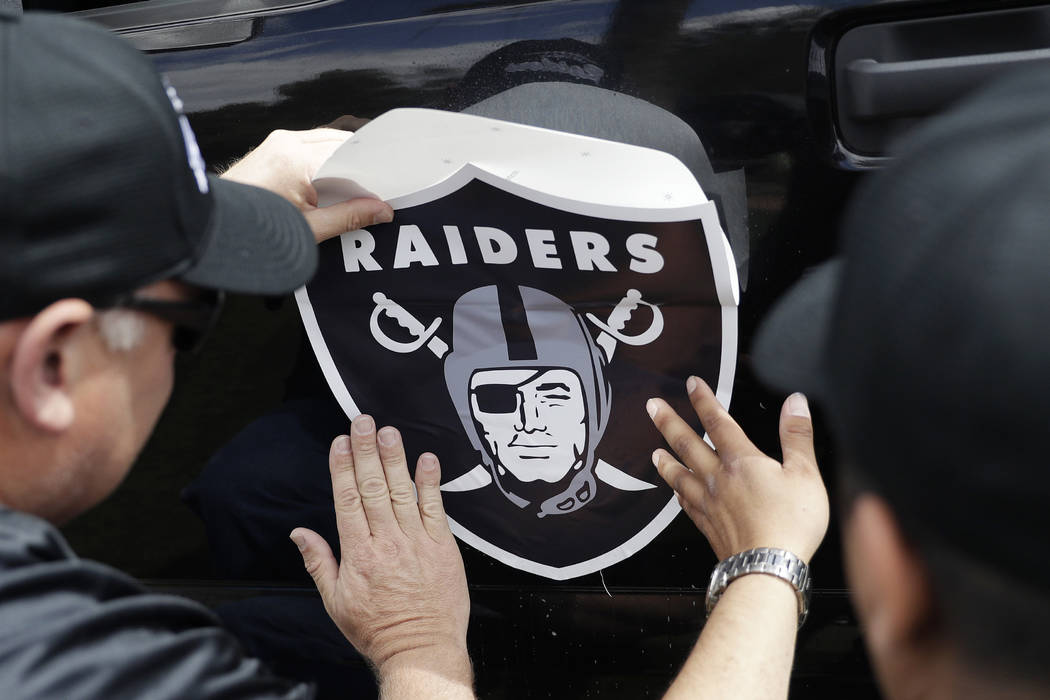 Members of a laborers union affix a Raiders logo to a truck, Monday, March 27, 2017, in Las Vegas. (John Locher/AP)