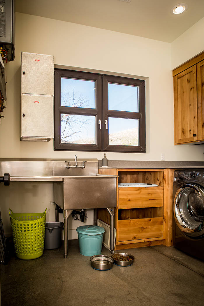 The laundry room is lined with knotty pine Alderwood cabinets, and a couple of insulated room service delivery bins obtained from the Debbie Reynolds Hotel serve as storage. (Tonya Harvey)