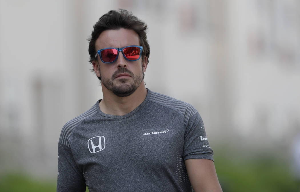 McLaren driver Fernando Alonso of Spain, walks in the paddock prior to a news conference, ahead the Bahrain Formula One Grand Prix at the Formula One Bahrain International Circuit in Sakhir, Bahra ...