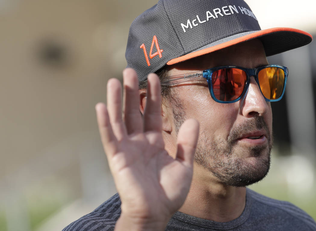 McLaren driver Fernando Alonso of Spain, gives an interview to a reporter in the paddock, ahead of the Bahrain Formula One Grand Prix at the Formula One Bahrain International Circuit in Sakhir, Ba ...