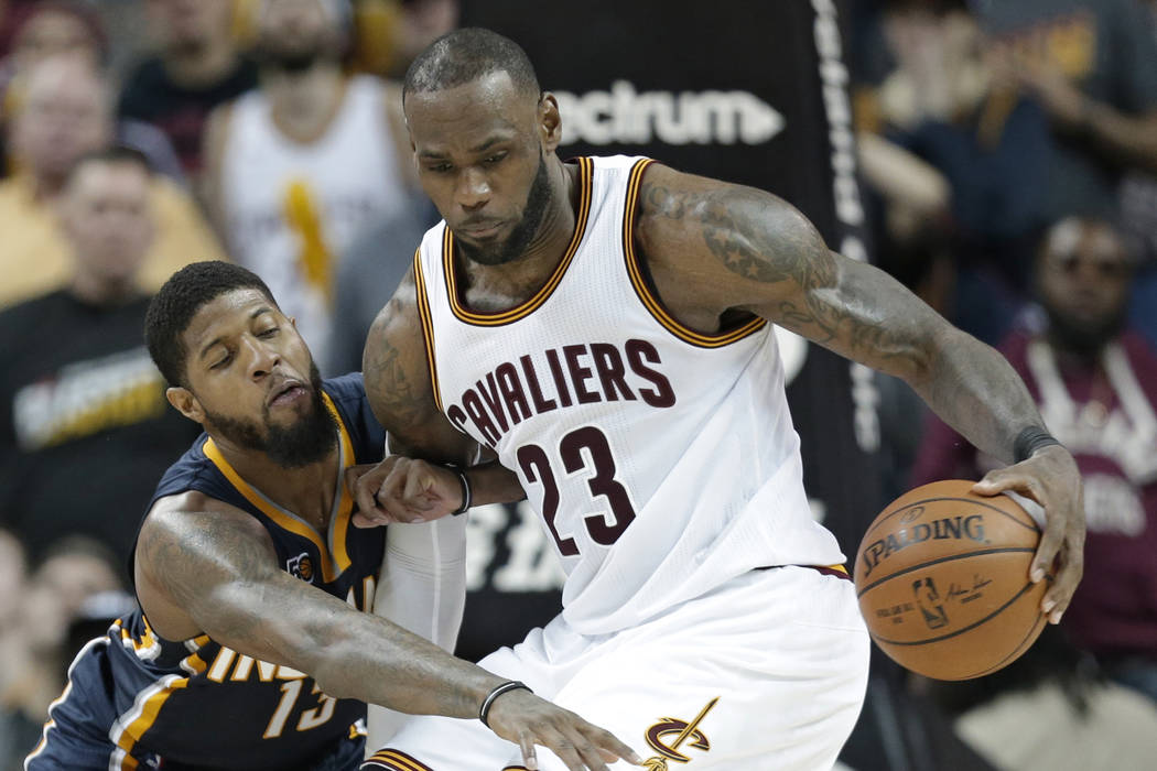 Indiana Pacers' Paul George, left, reaches for the ball as Cleveland Cavaliers' LeBron James drives to the basket in overtime during an NBA basketball game, Sunday, April 2, 2017, in Cleveland. Th ...