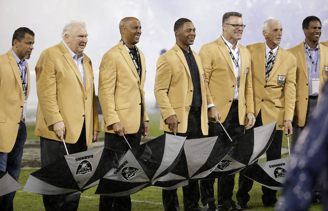 Hall of Famers Rod Woodson, from left, John Madden, James Lofton, Marcus Allen, Howie Long, Ray Guy, and Mike Haynes stand during a Hall of Fame ceremony for Guy during halftime of an NFL football ...