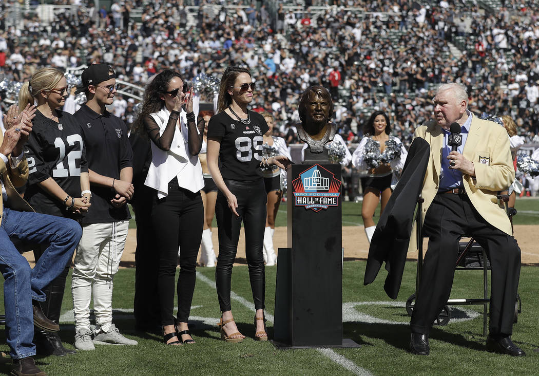 Former Oakland Raiders head coach John Madden, right, unveils a Pro Football Hall of Fame bust for former quarterback Ken Stabler next to Stabler's family at a ceremony during halftime of an NFL f ...